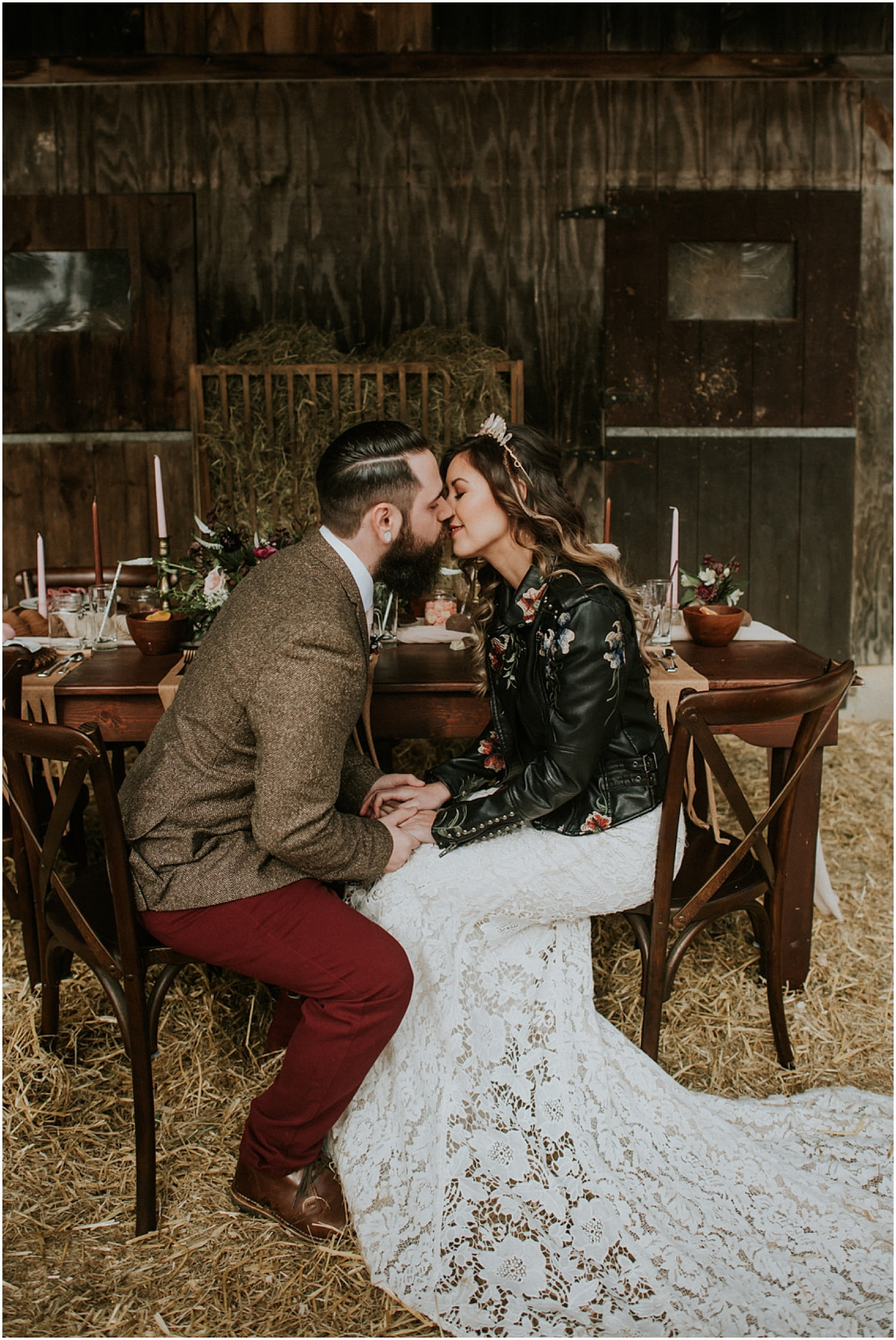 bride and groom sitting at their rustic tablescape