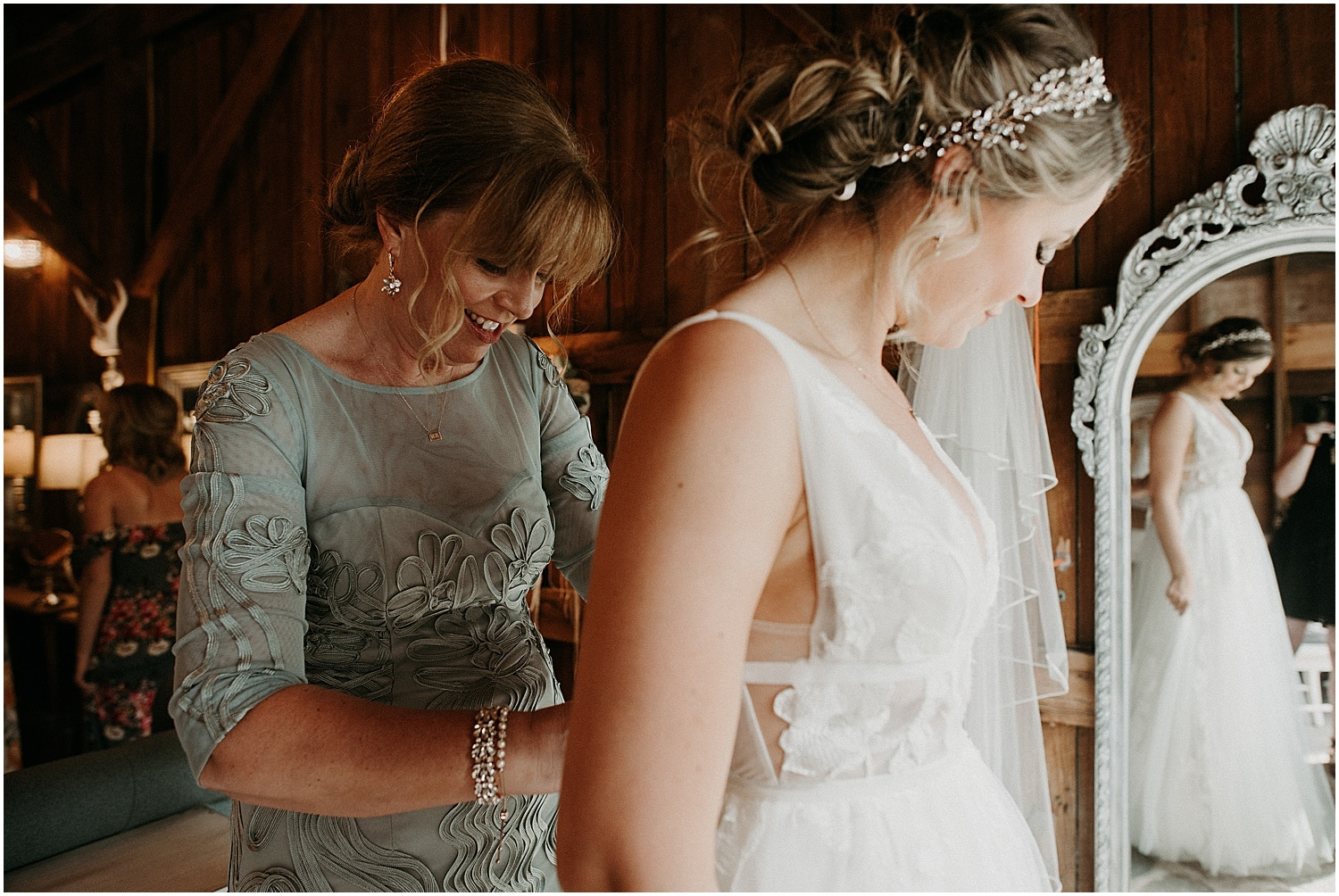 mother of the bride helps daughter button her dress at this Barn at Silver Oaks Wedding