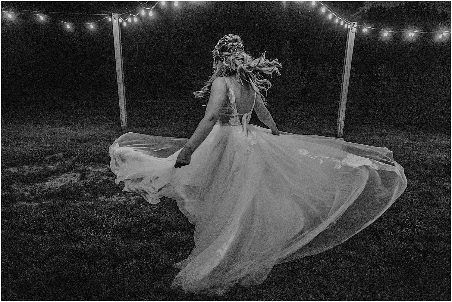 bride twirling under fairy lights at her Barn at Silver Oaks Wedding