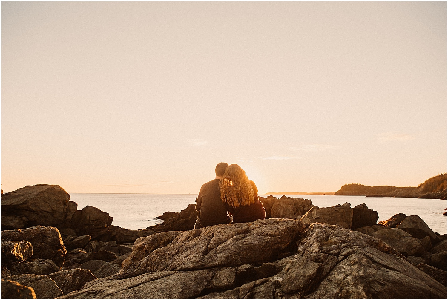 bride and groom watching sunset during their engagement pics