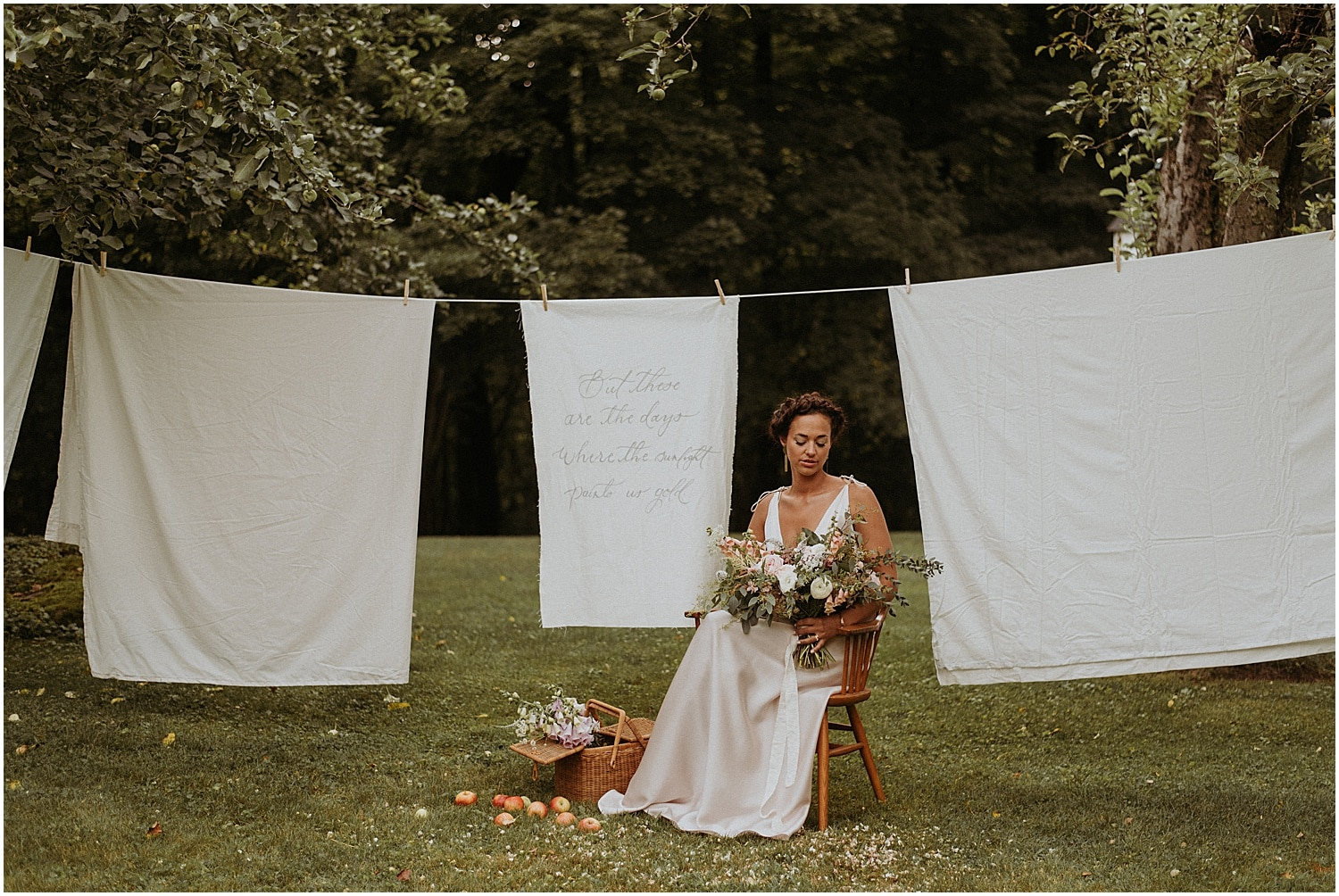 Bride holding a bouquet sitting in front of decorative drapes at Josias River Farm Bridal