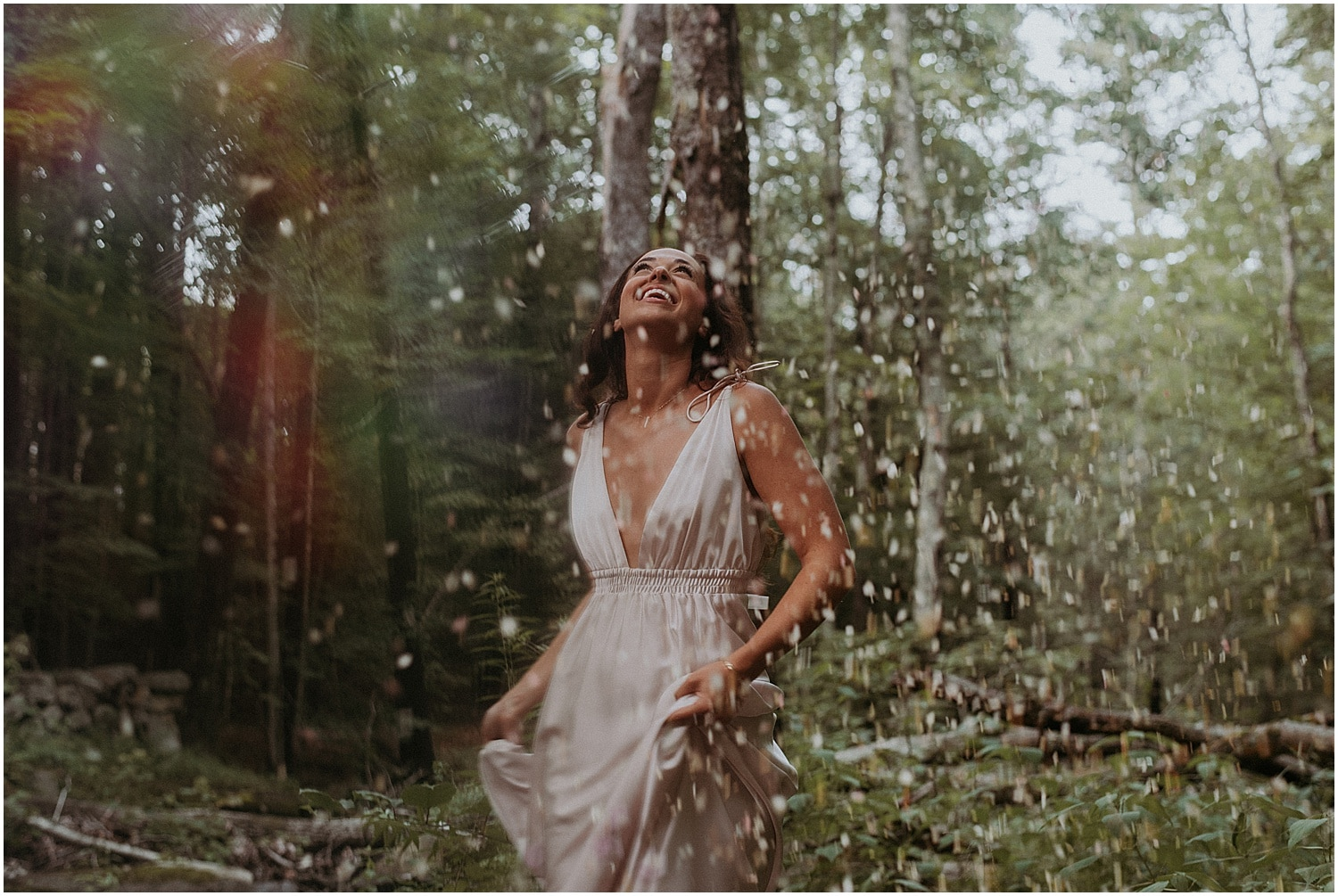 Bride kicking waters into the air in the woods