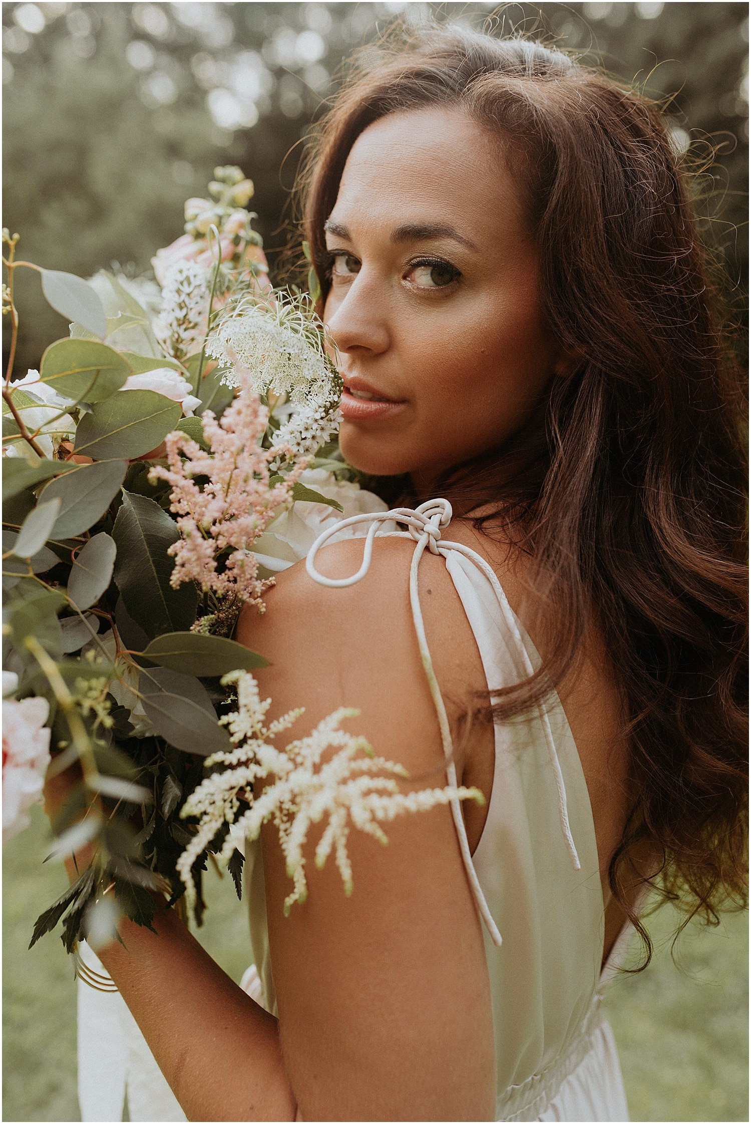Close up of a long haired bride holding her spring bouquet at this Josias River Farm Bridal Shoot