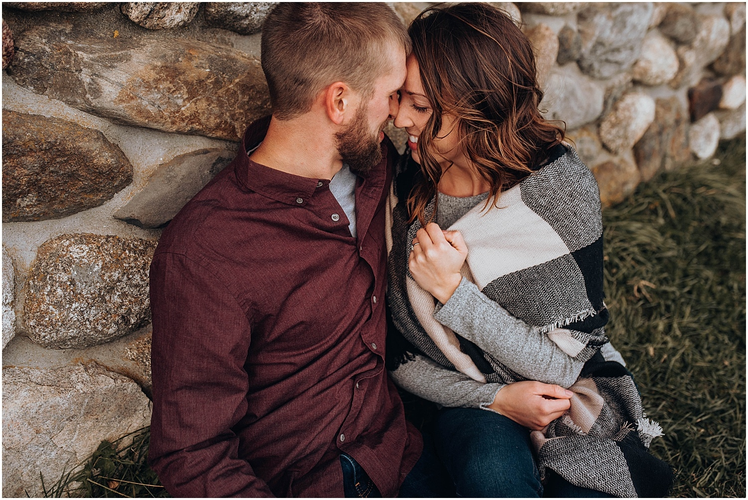cuddling against a rock wall at their Rockland Maine Engagement session