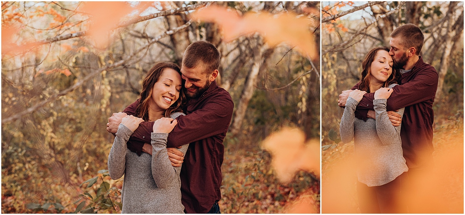 couple snuggling between leaves at their Rockland Maine Engagement session