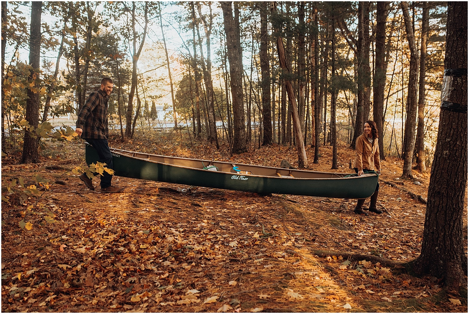 couple carrying a canoe together to the water at their Rockland Maine Engagement photo session