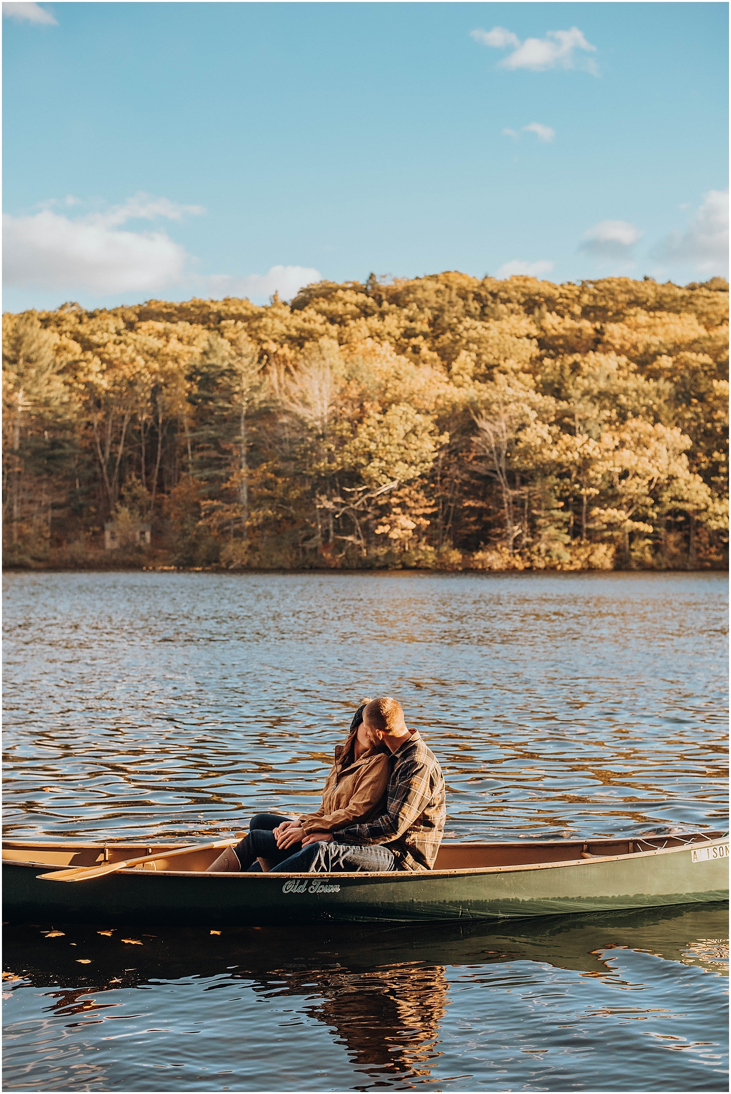 couple snuggling in a canoe on a lack in rockland maine