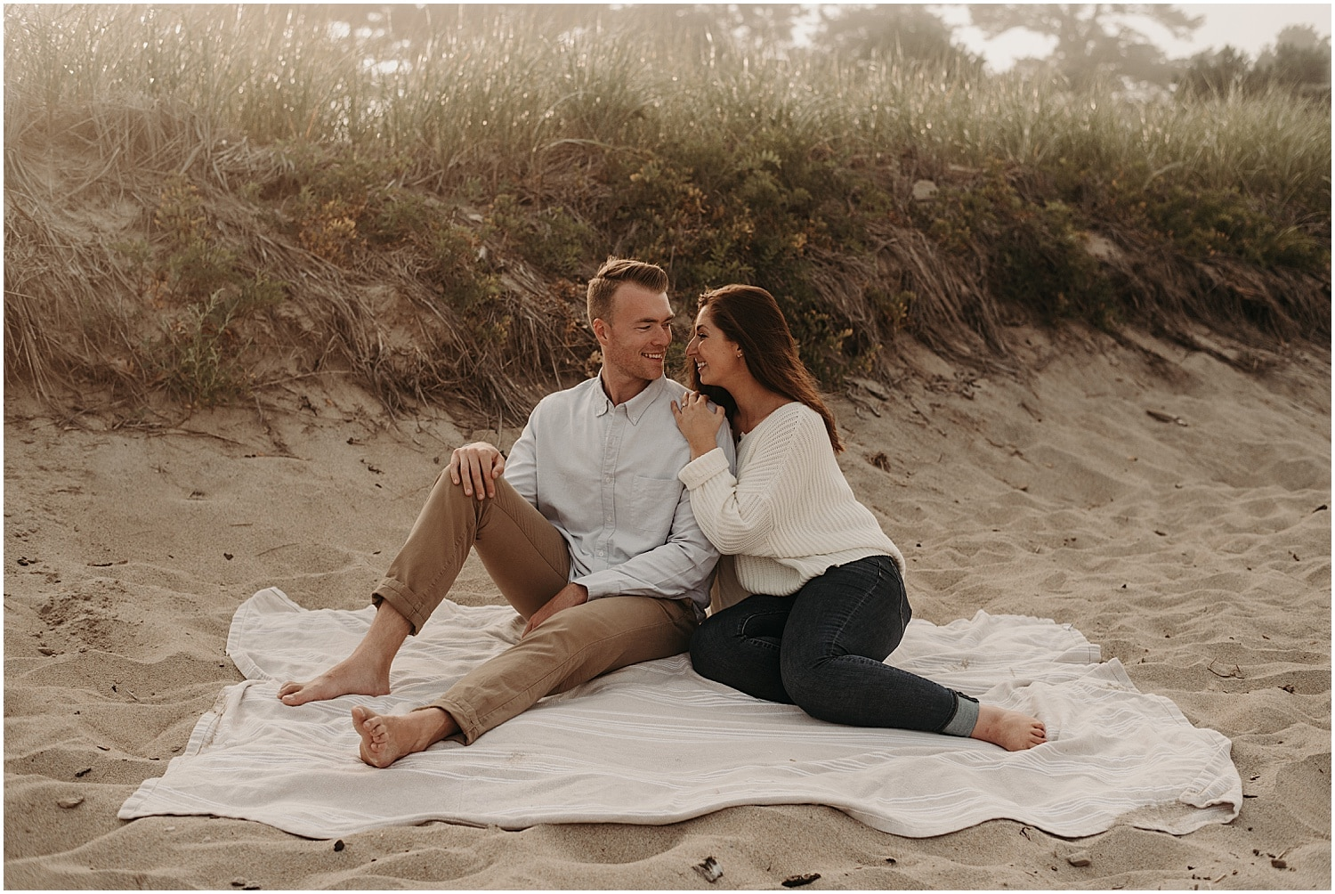 couple sitting on the blanket on the beach at their Ferry Beach Engagement session