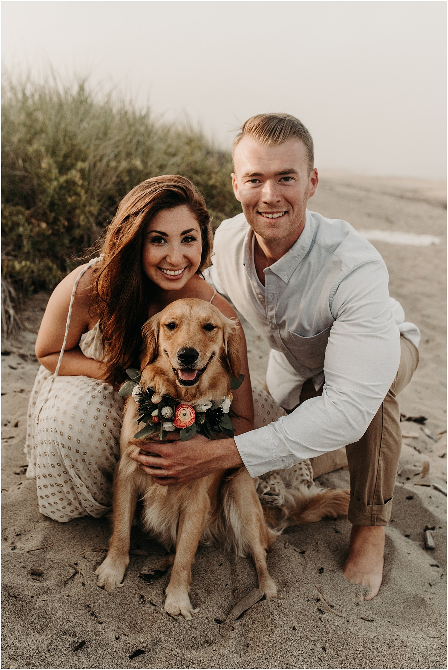 man and woman with their dog with a floral collar at their Ferry Beach Engagement session