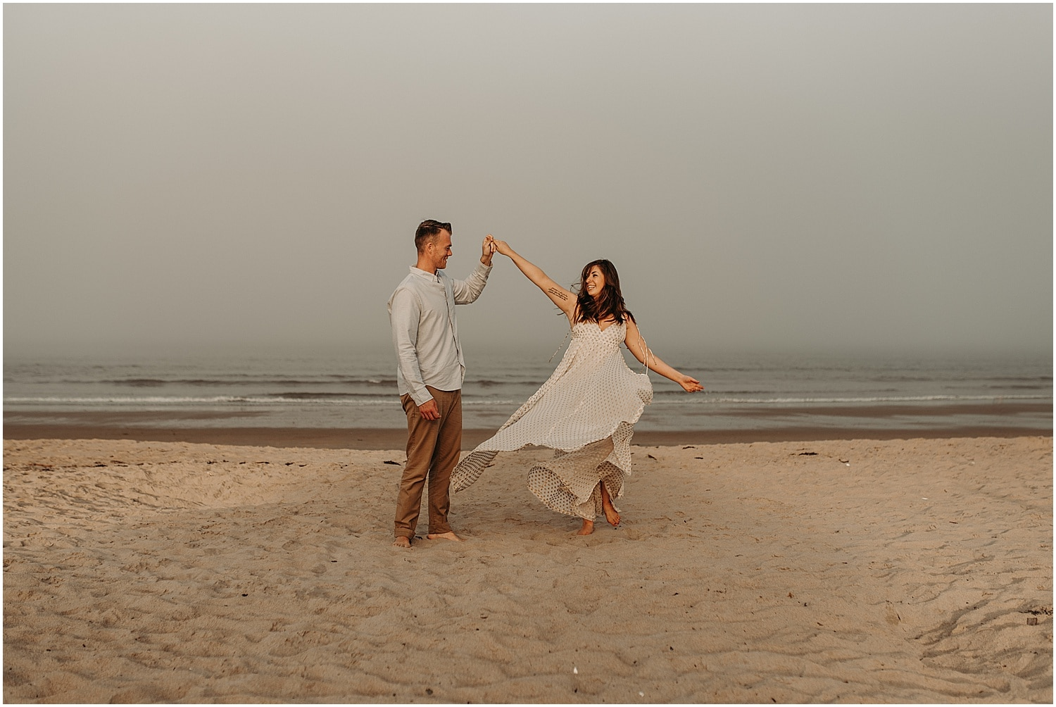man and woman dancing on the beach at their Ferry Beach Engagement