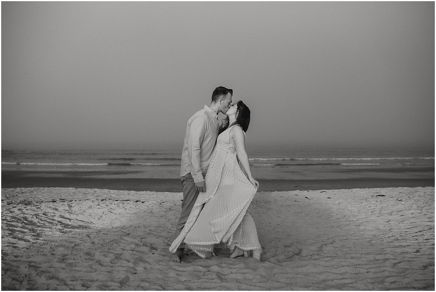 black and white of couple kissing on the beach at their Ferry Beach Engagement session