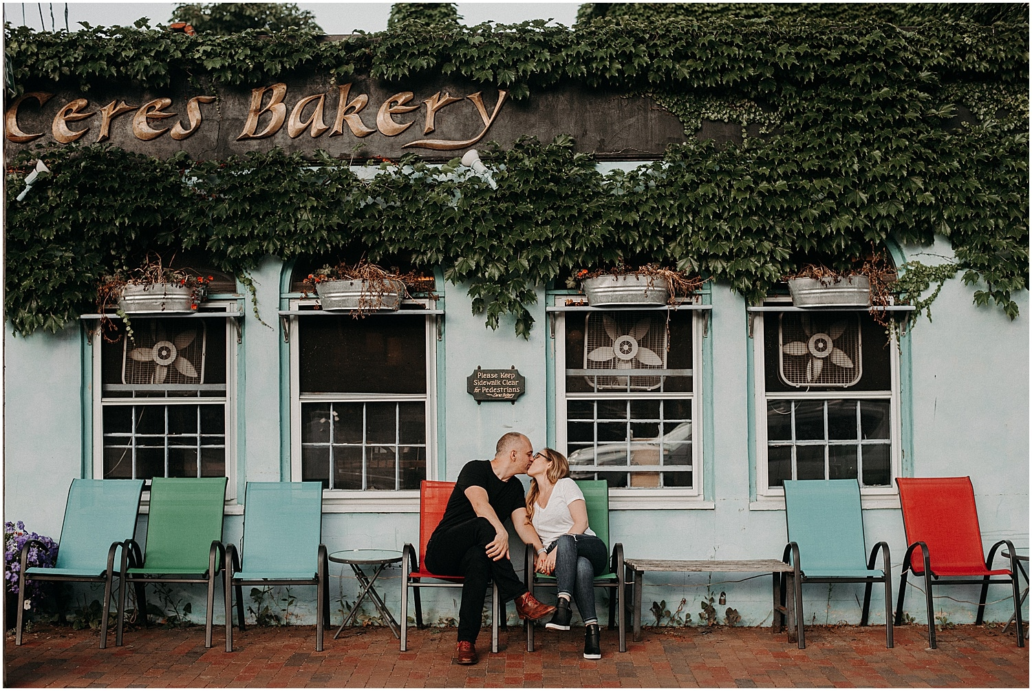 man and woman kissing in front of cool bakery at their Portsmouth Engagement Photography