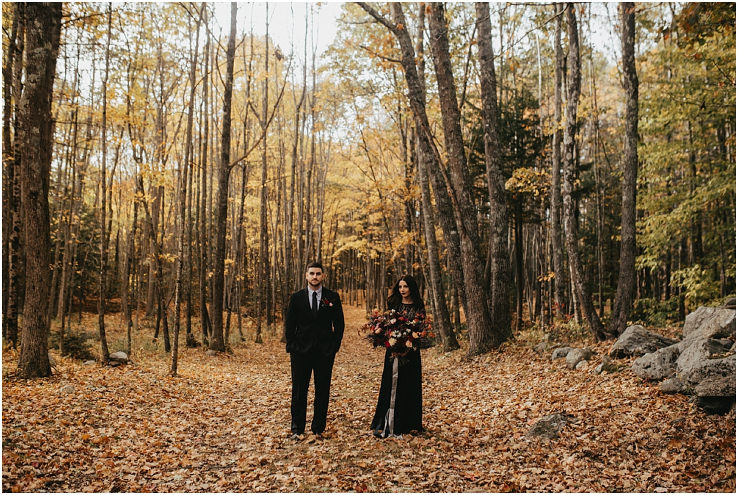 couple standing in the forest during their halloween wedding inspiration shoot
