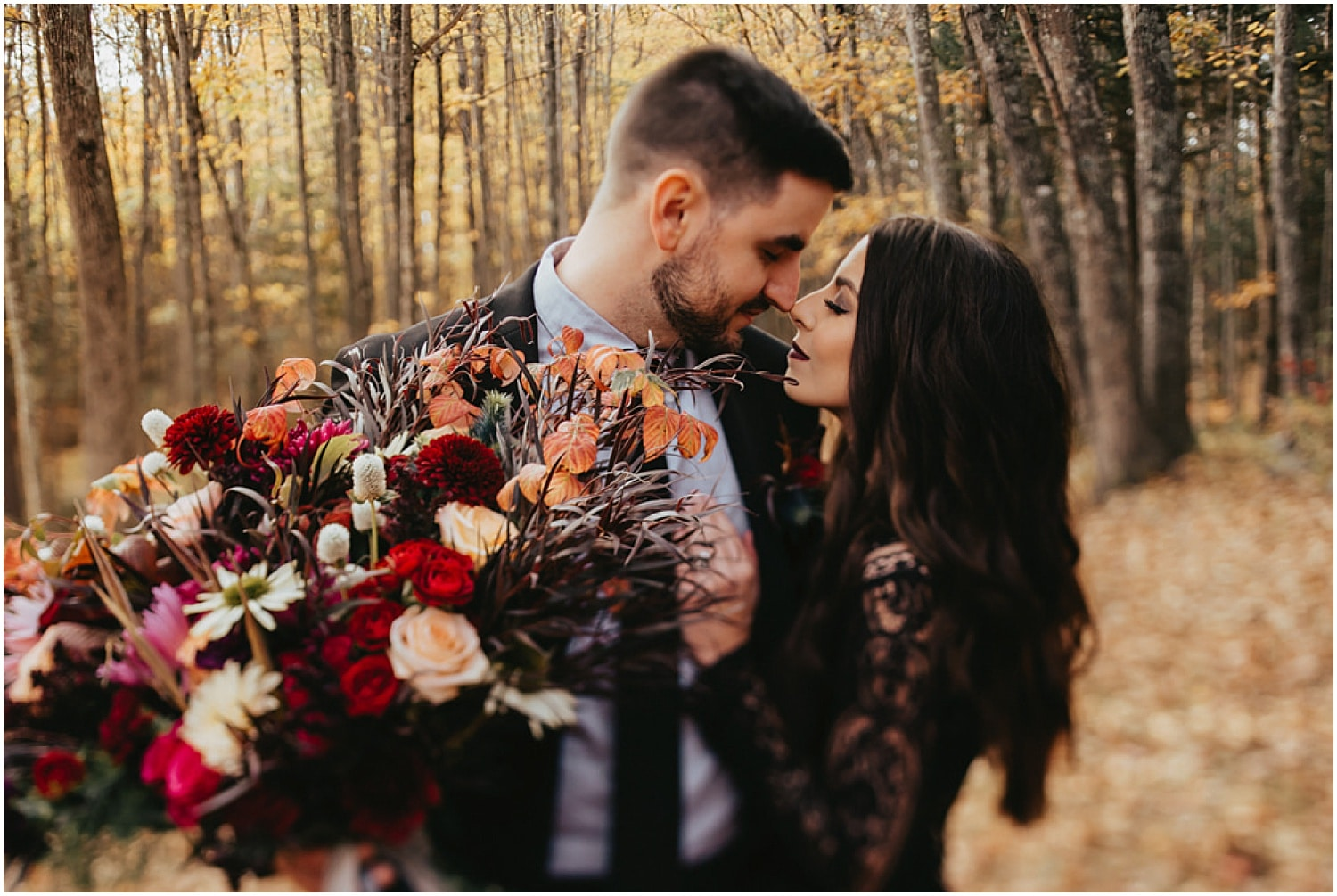 couple nuzzling noses during this halloween wedding inspiration shoot