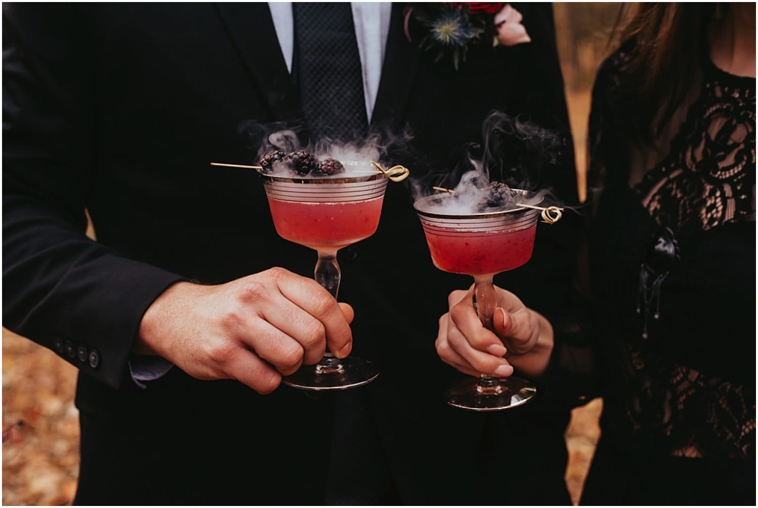 smoking spooky drinks held by bride and groom for halloween wedding inspiration